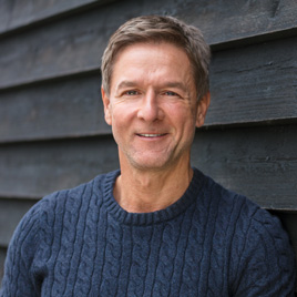 man smiling while leaning against wall