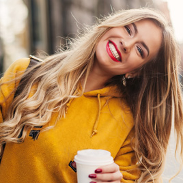 woman smiling while walking with coffee in hand